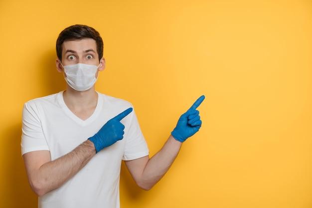 얼굴 마스크와 의료 장갑을 착용하고 노란색에 공간을 복사를 가리키는 충격 백인 남자