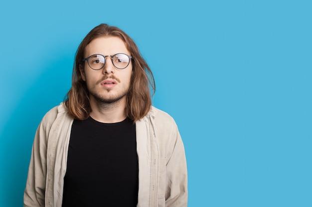 長い髪と眼鏡でショックを受けた白人男性は、空きスペースのある青いスタジオの壁にカメラを見ています