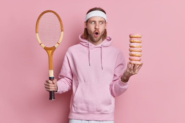Shocked caucasian man with stunned face expression has break during tennis game holds racket and pile of doughnuts leads active life