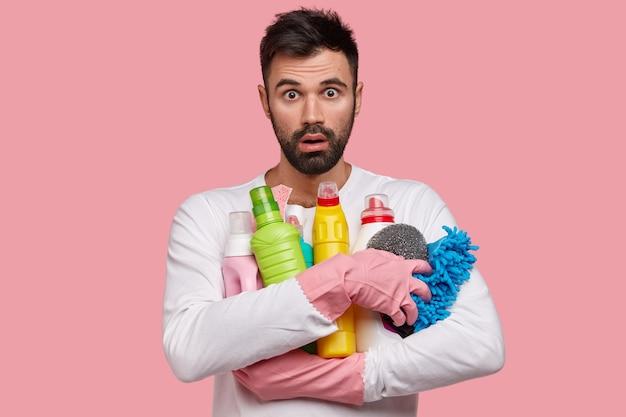 ショックを受けた白人の無精ひげを生やした男は、掃除用品、皿洗い用のスポンジ、カジュアルな服装、愚痴を見つめ、雑用をします