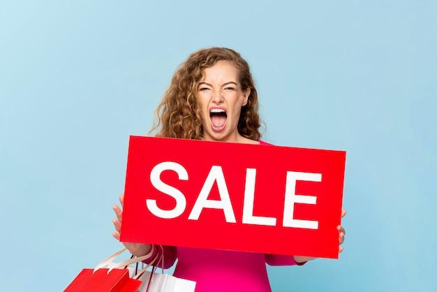 水色のブルーウォールに分離された赤い販売標識を示す買い物袋を運ぶショックを受けた白人女性