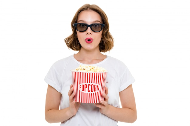 Shocked caucasian woman holding pop corn wearing 3d glasses
