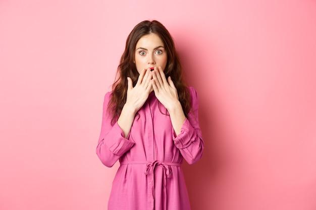 가벼운 봄 드레스에 충격을받은 백인 여자, 헐떡이며 손으로 입을 덮고, 불신과 충격으로 쳐다보고, 분홍색 벽 위에 서 있습니다.
