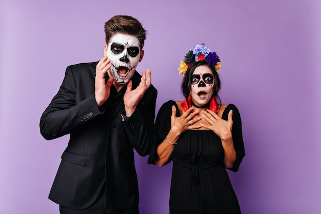 Shocked caucasian woman with black hair posing in halloween costume. surprised zombie guy standing on purple wall with girlfriend.