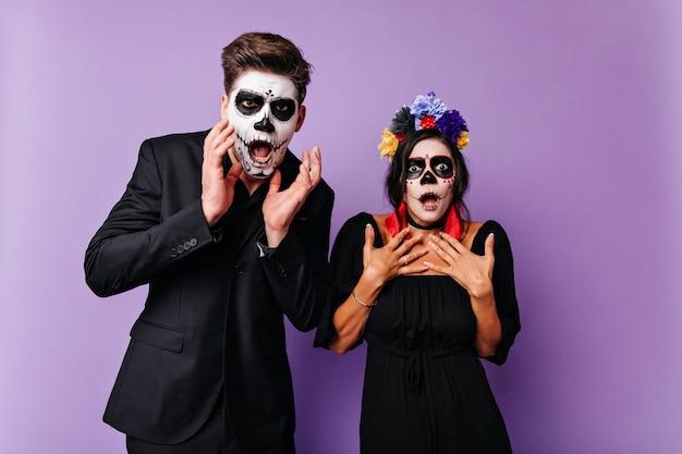 ハロウィーンの衣装でポーズをとって黒髪のショックを受けた白人女性。ガールフレンドと一緒に紫色の壁に立っている驚いたゾンビの男。