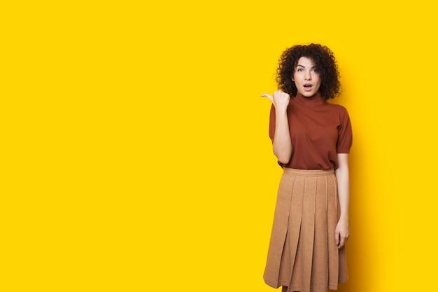 Шокированная кавказская женщина с вьющимися волосами указывает на желтое свободное пространство рядом с ней