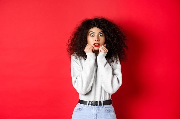 巻き毛の髪型でショックを受けた白人女性、印象的なものを見て、あえぎ驚いて、プロモーションのオファーをチェックして、赤い背景。