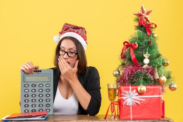 Signora affascinante scioccata in vestito con cappello di babbo natale e occhiali da vista che mostrano calcolatrice in ufficio su giallo isolato