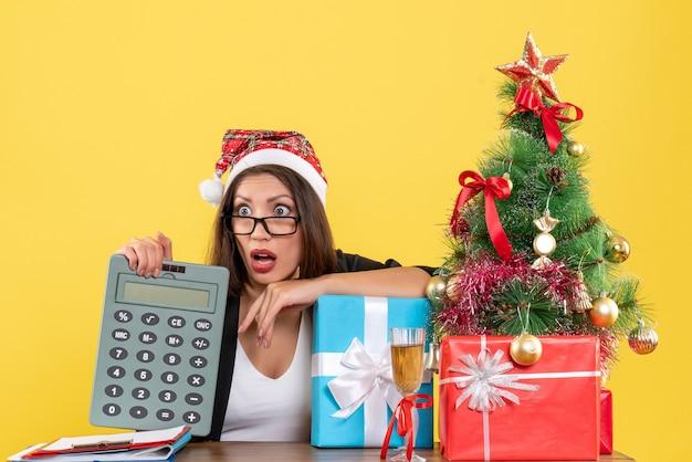 Signora affascinante scioccata in vestito con il cappello di babbo natale che mostra la calcolatrice nell'ufficio su colore giallo isolato