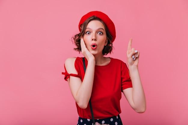 エレガントなベレー帽のポーズでショックを受けた魅力的な女性。フランスの衣装で魅力的な白人女性の屋内肖像画。