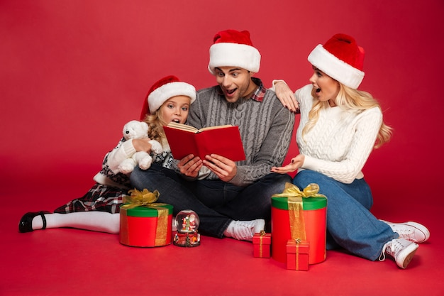 Shocked cheerful young family wearing christmas hats reading book.