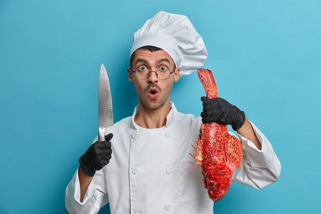 Shocked chef stares with great surprisement, holds sharp knife, whole fresh fish, prepares healthy food quickly, sea bass soup