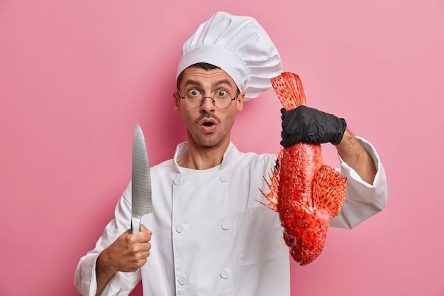 Chef scioccato in uniforme bianca e cappello, tiene il branzino rosso, coltello, va a cucinare zuppa di pesce, lavora con i guanti, lavora in un ristorante di frutti di mare, tiene una master class