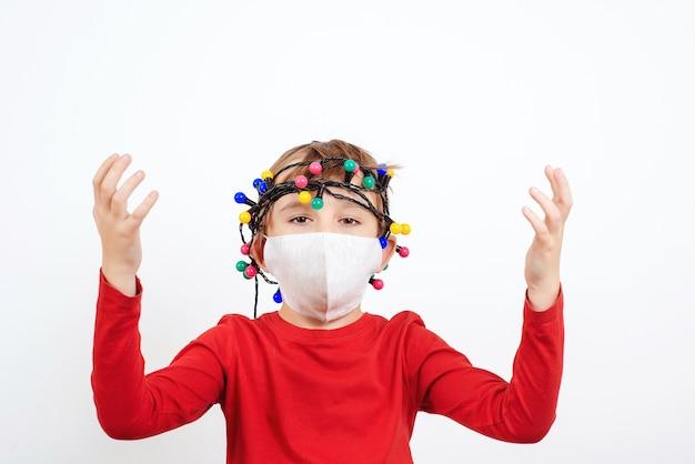 安全フェイスマスクを身に着けているショックを受けた子供。検疫中にお祝いの花輪を持つ疲れた子供。コロナウイルスパンデミック。否定的な感情を持つ不幸な少年