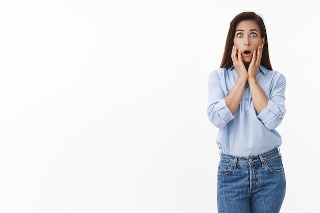 ショックを受けた心配しているブルネットの女性は、怖がって待ち伏せされた恐ろしいニュースを感じ、あえぎ、おびえ、顔に触れ、恐怖を正面から見つめ、驚いた、パニックに陥り、白い壁に立つ