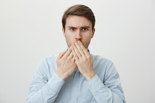 Шокированный обеспокоенный мужчина прикрывает рот руками, озабоченно хмурясь