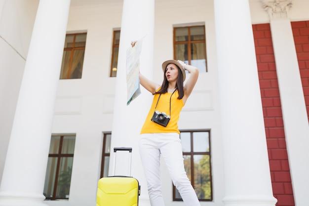屋外の都市地図を見て頭にしがみついているスーツケースとレトロなビンテージ写真カメラでショックを受けた旅行者の観光客の女性。週末の休暇で海外旅行する女の子。観光の旅のライフスタイル。