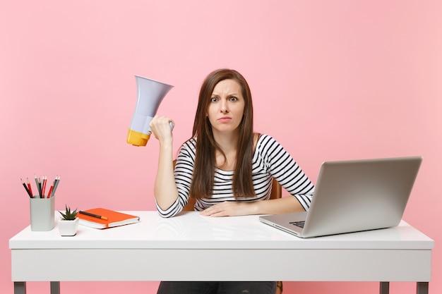 パステルピンクの背景に分離されたpcラップトップでオフィスの白い机でプロジェクトに取り組んで座っている間メガホンを保持しているショックを受けた心配の女性。業績ビジネスキャリアコンセプト。スペースをコピーします。