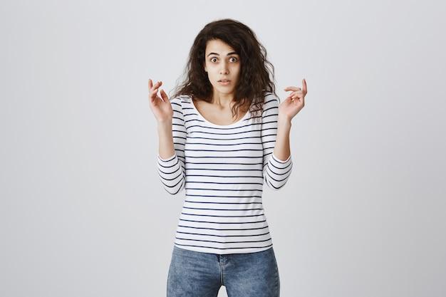 驚いた手を挙げてショックを受けた心配する女性