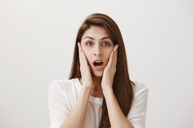 La donna scioccata e preoccupata guarda allarmata, esprime empatia e preoccupazione