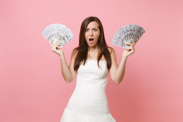 Shocked concerned woman with opened mouth in white dress holding bundle lots of dollars, cash money