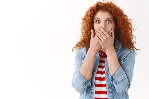 Scioccato preoccupato giovane amica rossa che reagisce scioccante notizie terrificanti ansimando spaventato chiudere bocca mani occhi spalancati frustrato in piedi muro bianco preoccupazione alito cattivo