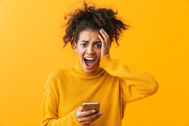 Shocked confused african woman wearing sweater standing isolated, holding mobile phone
