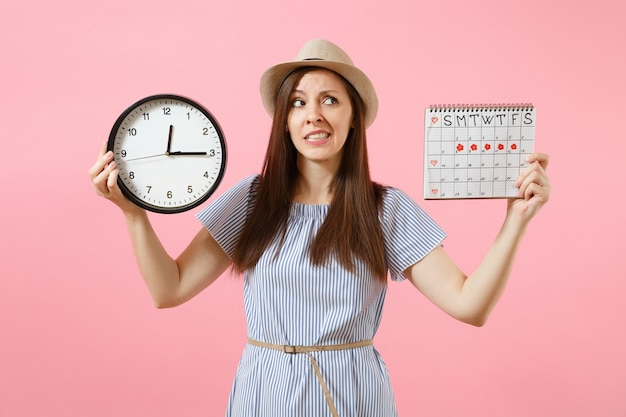 Shocked confused sad woman in blue dress holding round clock, periods calendar for checking menstruation days isolated on trending pink background. medical healthcare gynecological concept. copy space