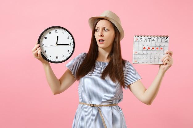 둥근 시계를 들고 있는 파란 드레스를 입은 혼란스러운 슬픈 여성, 유행하는 분홍색 배경에 격리된 월경일을 확인하기 위한 기간 달력. 의료 의료 부인과 개념입니다. 복사 공간