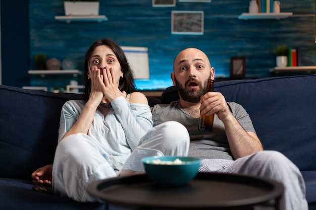 Shocked confused young couple watching documentary movie at tv