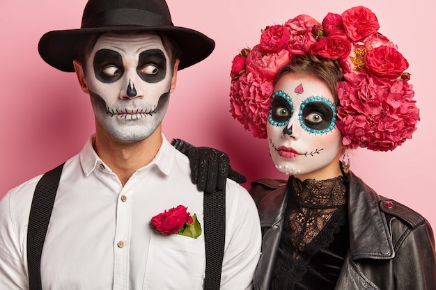Shocked couple have scary face expressions, funky makeup and costumes, wear black and white attire decorated with red flowers, pose together in studio against pink wall