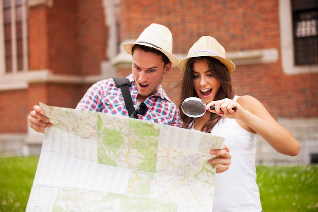 Shocked couple looking at map through magnifying glass