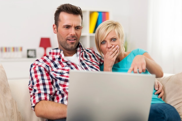 Shocked couple sitting on sofa and looking at laptop