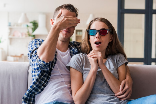 Shocked couple watching film and hugging on couch