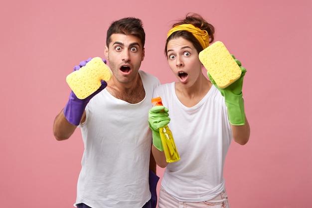 スポンジと洗剤のクリーニングウィンドウでショックを受けたカップル。掃除の男性と女性がさり気なく着替えて仕事にびっくり。人、仕事、家事、家のコンセプト