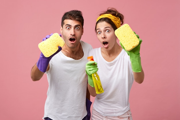 Shocked couple with sponges and detergent cleaning windows. man and female from cleaning service dressed casually being surprised to see much work. people, work, housekeeping and home concept