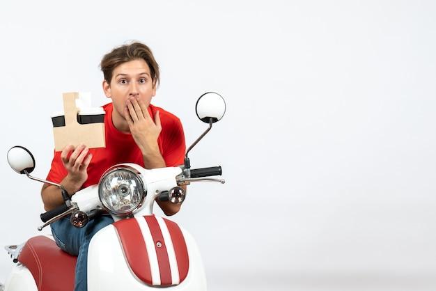 Uomo di corriere scioccato in uniforme rossa che si siede sulla moto che consegna gli ordini su priorità bassa bianca