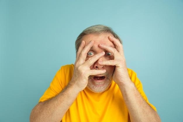 手で顔を覆ってショックを受けた。青いスタジオの背景に白人男性の肖像画。黄色いシャツのポーズで美しい男性モデル。