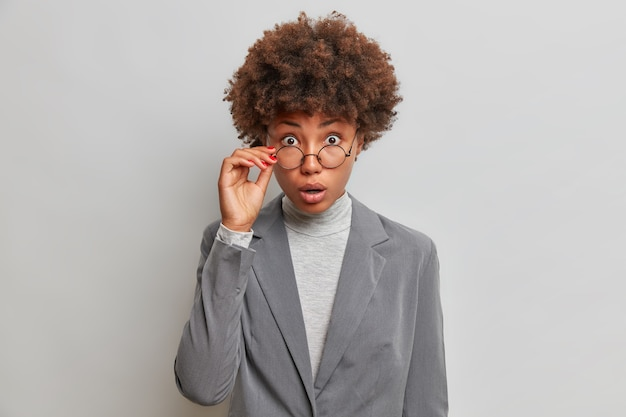 Shocked curly businesswoman with curly hair stares through spectacles dressed formally reacts on amazing news isolated over grey wall