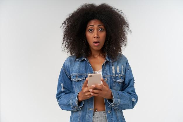白い壁の上に立っている間、スマートフォンを手に持って、突然のニュースを読んで、目を大きく開いたカジュアルな髪型のショックを受けた巻き毛の暗い肌の女性