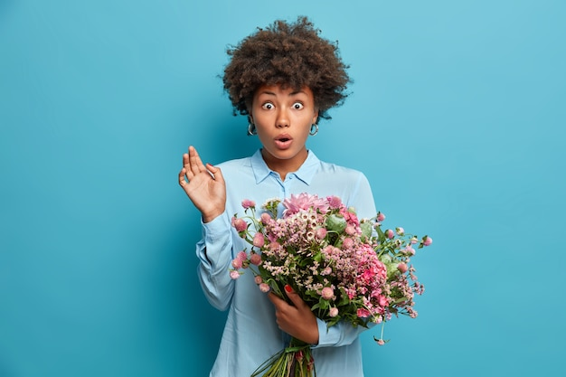 ショックを受けた巻き毛のアフロアメリカンの女性は、見知らぬ人から花束を受け取り、予期せぬ配達を受けたときにバグのある目を凝視し、スタイリッシュな青いシャツを着て、屋内に立っています。花のコンセプト