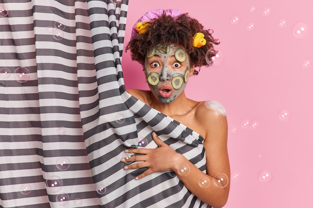 Шокированная кудрявая женщина пристально смотрит в камеру в камеру и удивлена, что кто-то вошел в ванную, принимает душ и проходит косметические процедуры, изолированные на розовой стене с мыльными пузырями