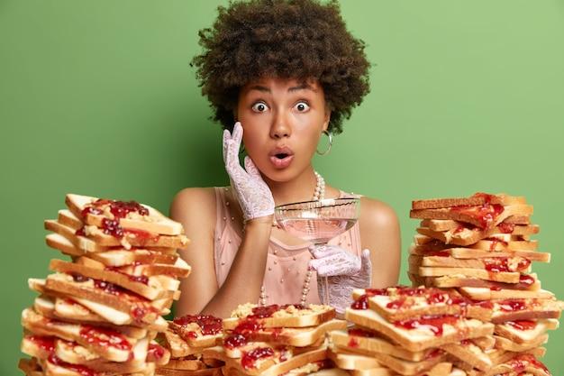 ショックを受けた巻き毛の若い女性は、顔に手を置いて不思議な飲み物から口を開けますカクテルは甘いジャムとパンの大きなスタックに対してジュエリーポーズでエレガントな服を着ています。