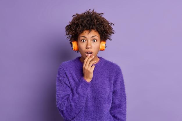 La giovane donna dai capelli ricci scioccata con i capelli afro fissa sorprendentemente la telecamera tiene la bocca aperta indossa le cuffie stereo maglione viola ascolta notizie scioccanti alla radio pose al coperto. omg concetto
