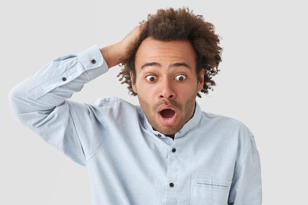 ショックを受けた巻き毛の男は恐ろしい表情で見え、頭を抱え、バグのある目で見つめ、何かひどいことを聞きます
