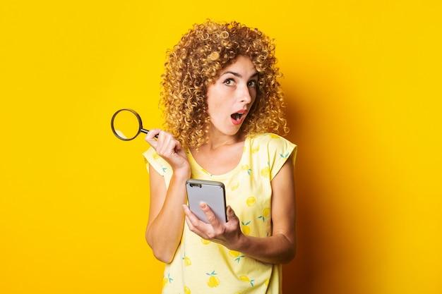 Шокированная кудрявая молодая женщина, держащая увеличительное стекло и телефон на желтой поверхности