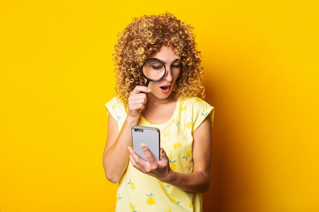 Shocked curly young woman looking with a magnifying glass into the phone on a yellow surface