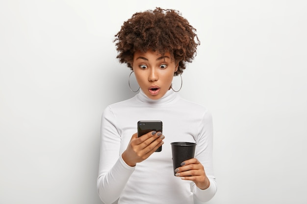 Потрясенная кудрявая молодая женщина реагирует на сообщение, читает плохие новости, держит в руках современный сотовый, пьет кофе на вынос, носит белую удобную одежду, позирует. концепция современных технологий