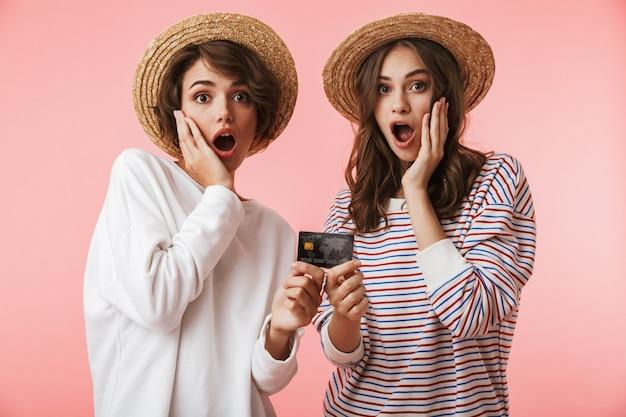 クレジットカードを持っているショックを受けたかわいい若い女性の友人。