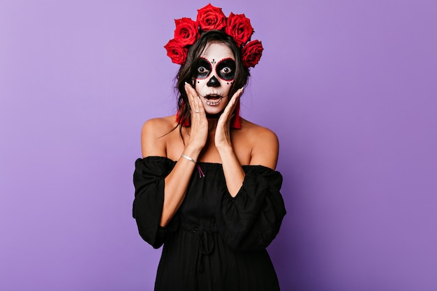 Shocked dark-eyed lady posing with mouth open in halloween. indoor shot of frightened female zombie with roses in hair.